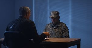 Expressive policeman examining military man in interview room royalty free stock photography