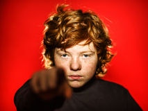 Expressive red-haired teenage boy showing emotions in studio. Isolated on red stock photo