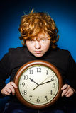 Expressive red-haired teenage boy showing time on big clock Royalty Free Stock Images