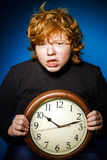 Expressive red-haired teenage boy showing time on big clock Royalty Free Stock Photography