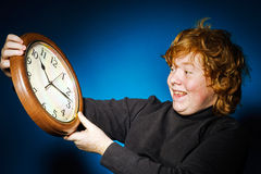 Expressive red-haired teenage boy showing time on big clock Stock Photo