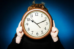Expressive red-haired teenage boy showing time on big clock Stock Photography