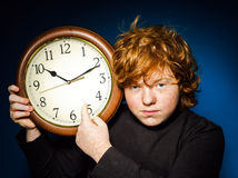 Expressive red-haired teenage boy showing time on big clock Stock Photos
