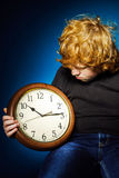 Expressive red-haired teenage boy showing time on big clock Royalty Free Stock Image