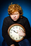 Expressive red-haired teenage boy showing time on big clock Stock Image