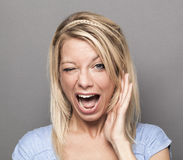 Expressive 20s blonde girl winking for humor Stock Photos