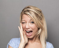 Expressive 20s blonde girl winking for satisfaction Royalty Free Stock Photography