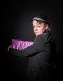 Expressive teenage boy holding box with gift Stock Image