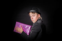 Expressive teenage boy holding box with gift Royalty Free Stock Photo