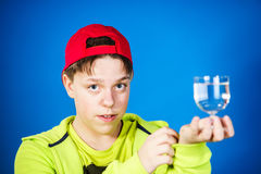 Expressive teenage boy posing with glass of water Royalty Free Stock Image