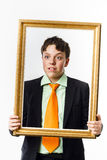 Expressive teenage boy posing with picture frame Stock Images
