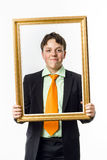 Expressive teenage boy posing with picture frame Royalty Free Stock Image