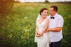 Expressive wedding couple on the meadow during outdoor photosession Stock Images
