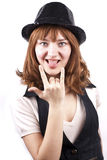 Expressive woman with her tongue out isolated. Pretty expressive woman with her tongue out, in a black cap, over white background, metal gesture royalty free stock photography