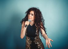 Expressive woman lady girl singing looking at you with microphone in hand dancing royalty free stock images
