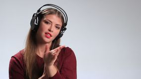Expressive woman listening music in headphones stock video