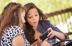 Excited Young Adult Girlfriends Using Their Smart Phone royalty free stock photos