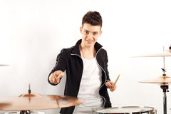 Expressive young drummer playing at the drums with drum stick Royalty Free Stock Image