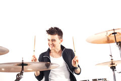 Expressive young drummer playing at the drums with drum stick Royalty Free Stock Photography
