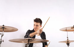Expressive young drummer playing at the drums with drum stick Royalty Free Stock Photos