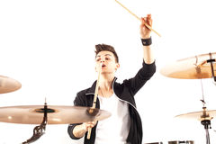 Expressive young drummer playing at the drums with drum stick Stock Photo