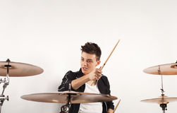 Expressive young drummer playing at the drums with drum stick Stock Photography