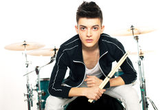Expressive young drummer playing at the drums with drum stick Stock Image