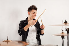 Expressive young drummer playing at the drums with drum stick Royalty Free Stock Images