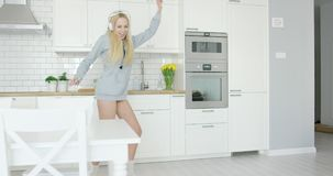 Expressive young girl dancing in kitchen stock video footage