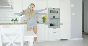Expressive young girl dancing in kitchen stock images