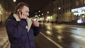 Expressive young man talks on phone at blurred city background. Young man is talking on phone at night city background. The man actively gesticulates hands and stock video footage