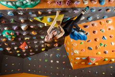 Expressive young woman bouldering in climbing gym Stock Image