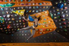 Young woman falling down while bouldering in indoor climbing gym Stock Image