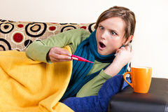 Expressive young woman having flu and checking thermometer Royalty Free Stock Photo