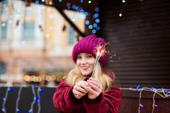Expressive blonde girl holding glowing Bengal lights at the Chri Royalty Free Stock Photography
