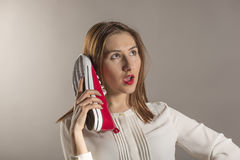 Expressive young woman. Young woman using a red shoe like a telephone holding it near her face and talking, studio shot against gray background Stock Photo