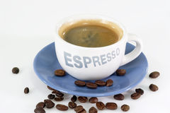 Expresso. Coffee  over roasted coffee beans Royalty Free Stock Photo