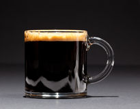 Expresso Coffee in glass cup. Black expresso coffee with heady froth in a glass mug or cup royalty free stock images
