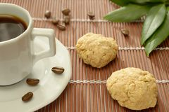 Expresso Coffee and Homemade Cookies. A cup of espresso coffee and two homemade oatmeal cookies. Some coffee beans and some green leaves on a bamboo set stock image