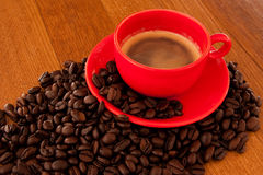 Expresso coffee in red cup. With coffee beans surrounding stock images