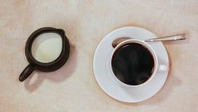 Expresso dans la tasse et soucoupe blanche avec la cuillère, lait dans le pot Photo stock
