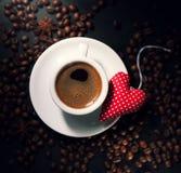 Expresso de café avec des grains de café sur un fond et une peluche rouge Photo stock