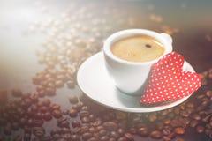 Expresso de café avec des grains de café sur un fond et une peluche rouge Photos libres de droits