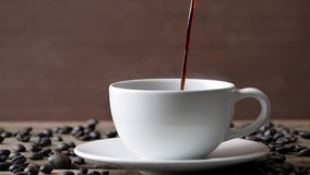 Expresso foncé chaud de tasse de café et de grain de café sur la table en bois banque de vidéos