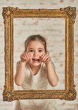 expressve可爱的年轻小女孩的室内画象 免版税库存照片