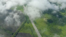 Expressway among fields in Europe from the air. Low cloudiness.