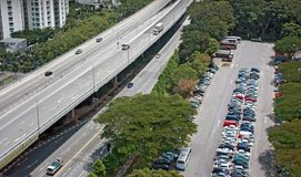 Expressway next to carpark. Arial helicopter view of a 2 way expressway next to a open air carpark royalty free stock photos