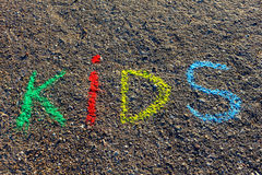 Exprima as CRIANÇAS escritas com os pastéis coloridos no asfalto, terra Fotos de Stock Royalty Free