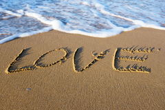 Exprima o AMOR escrito na areia na praia Imagens de Stock Royalty Free