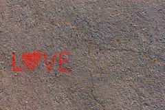 Exprima o AMOR escrito no asfalto, terra Cor vermelha do giz Fotografia de Stock Royalty Free